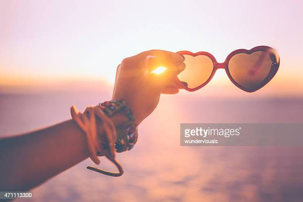 Hand holding heart-shaped sunglasses on a beach at sunset