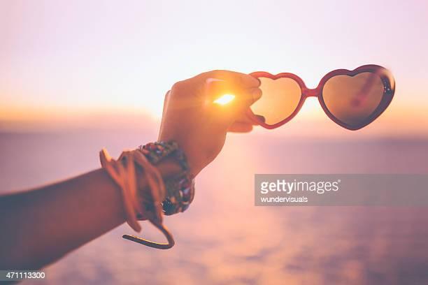 Mano che tiene gli occhiali da sole a forma di cuore su una spiaggia al tramonto