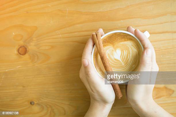 hand holding hot capucchino on wooden table