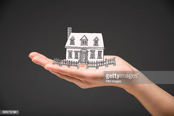 Hand holding illustrated house
