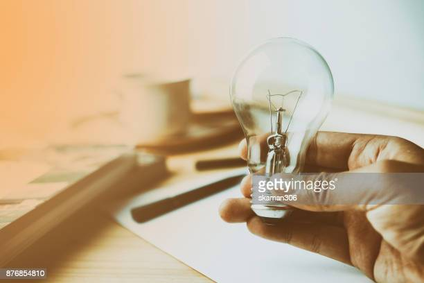 Hand holding Incandescent Lighting bulb on wooden workspace table