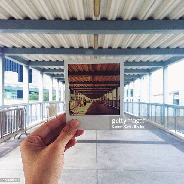 Hand holding instant photo picture at roofed walkway