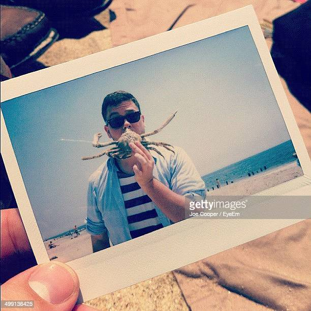 Hand holding instant photo picture of man with crab