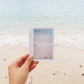 Hand holding instant photo picture of water against sea