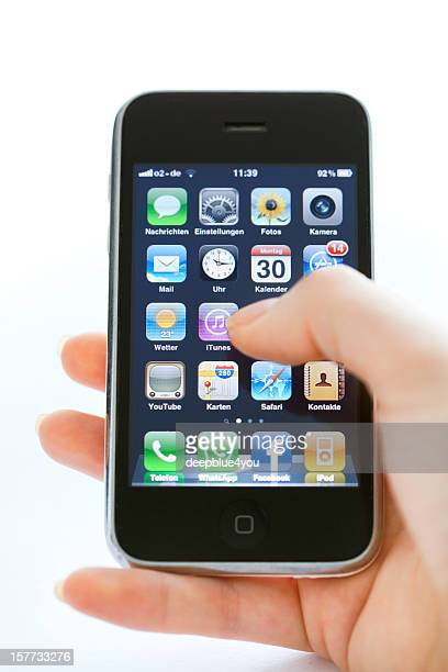 hand holding iPhone 3 typing on home screen