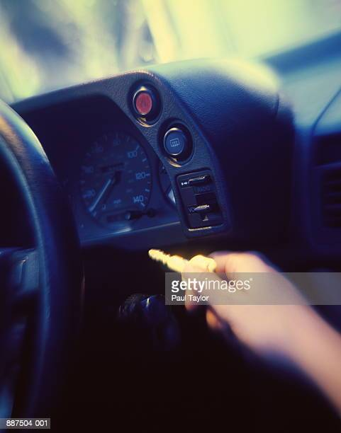 Hand holding key, reaching towards car ignition (blurred motion)