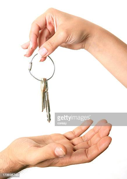 Hand holding keys over an open hand on white background