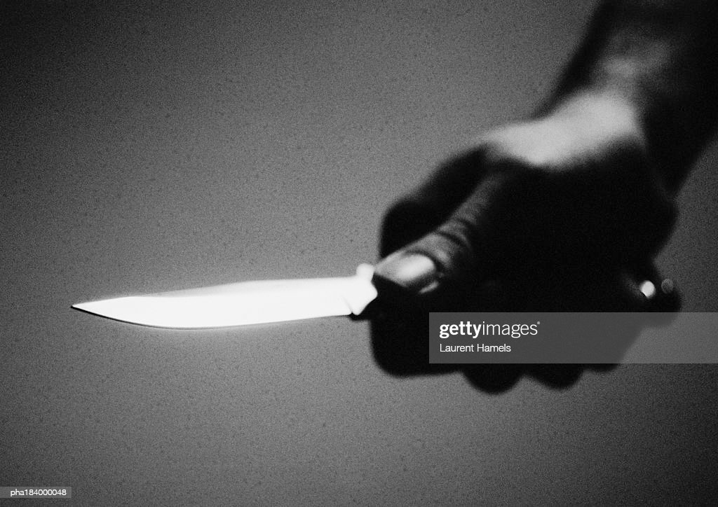 Hand holding knife, close-up, b&w