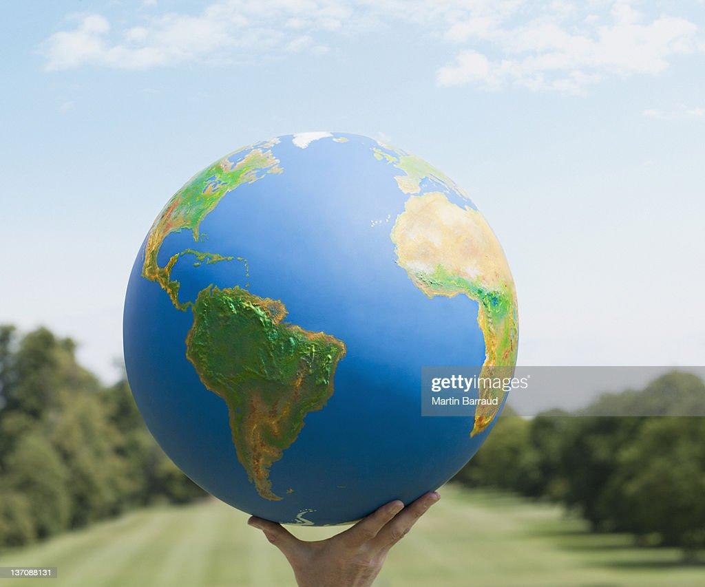 Hand holding large globe outdoors : Stock Photo