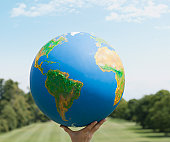 Hand holding large globe outdoors