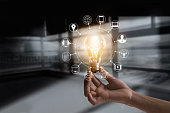 Hand holding light bulb with icons multimedia and customer network connection on dark room background