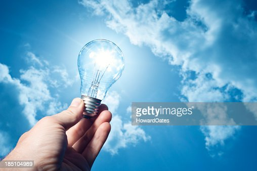 hand holding lightbulb to the sun