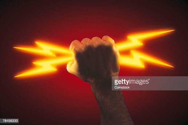 Hand holding lightning bolts