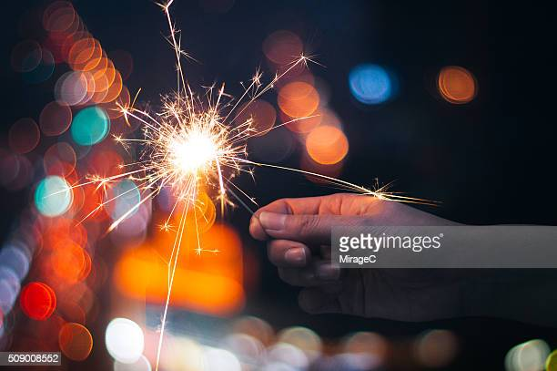 Hand holding Lit Sparkler at Night Bokeh