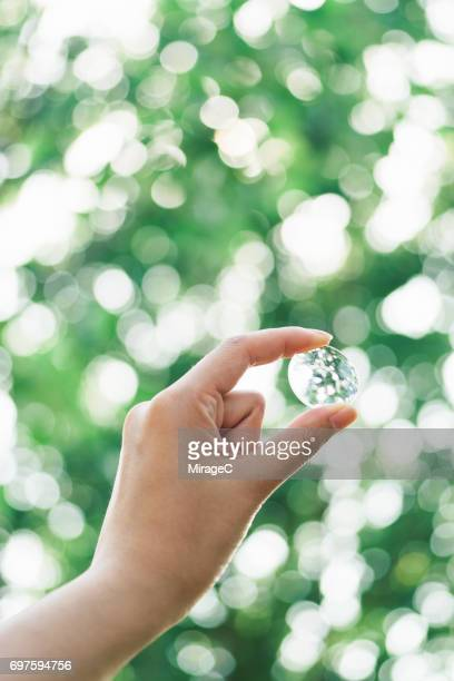 Hand Holding Magnifying Glass Against Green Trees Bokeh