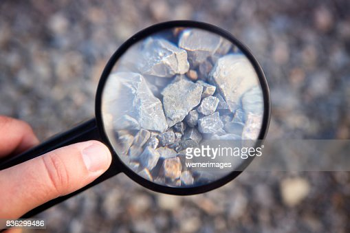 hand holding magnifying glass at stones : Stock Photo