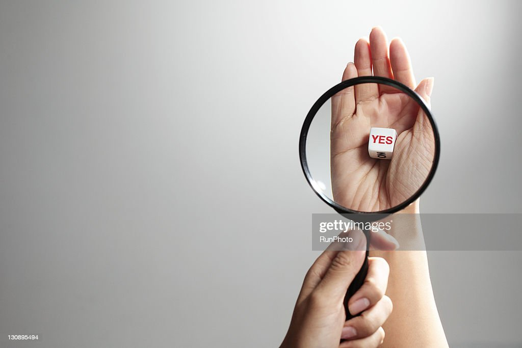 hand holding magnifying glass on dice with YES : Stock Photo