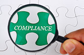 Hand Holding Magnifying Glass Seaching Missing Puzzle Pieces 'COMPLIANCE'