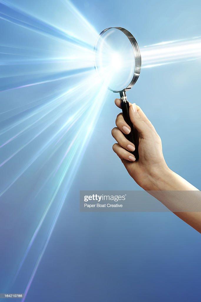 hand holding magnifying glass that breaks light