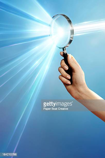 hand holding magnifying glass that breaks light