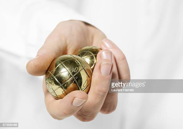 Hand holding metallic balls