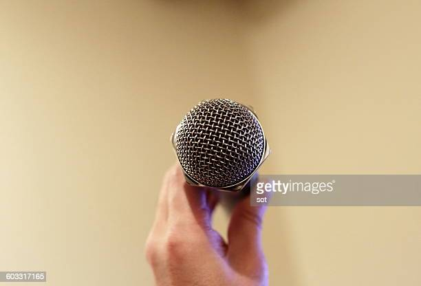 Hand holding microphone,close up