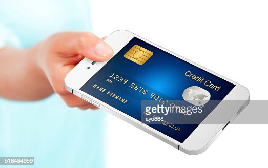 hand holding mobile phone with credit card isolated over white : Stock Photo