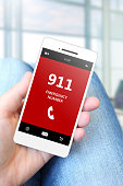 hand holding mobile phone with emergency number 911. focus on phone.
