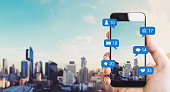 Hand holding mobile smart phone, with notification icons and city background