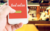 Hand holding mobile with Order food online with blur restaurant background, food online business concept.