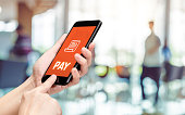 Hand holding mobile with pay word and bill icon feature with blur back office counter background,Digital Lifestyle concept.