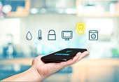 Hand holding mobile with Smart home control icon feature with blur kitchen background,Digital Lifestyle concept
