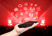 Hand holding mobile with Video marketing icon feature with blur live concert background,Digital Lifestyle concept.