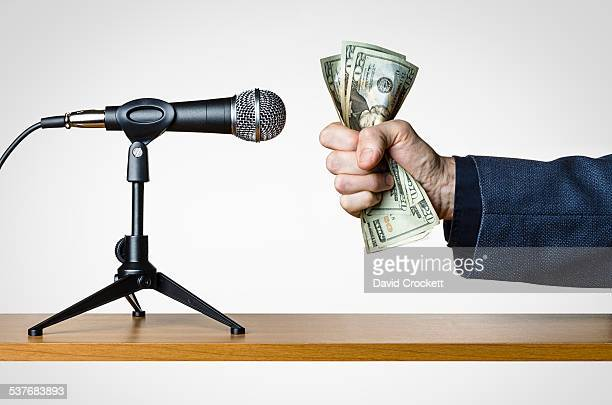 Hand holding money up to a microphone