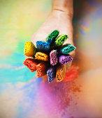 Hand holding multi coloured paint brushes
