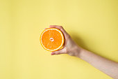 Hand holding orange on yellow background food concept