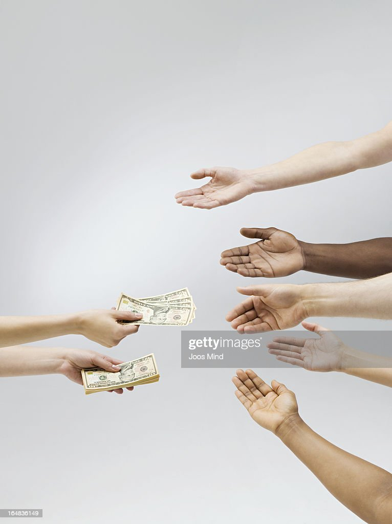 Hand holding out money, multiple hands receiving : Stock Photo