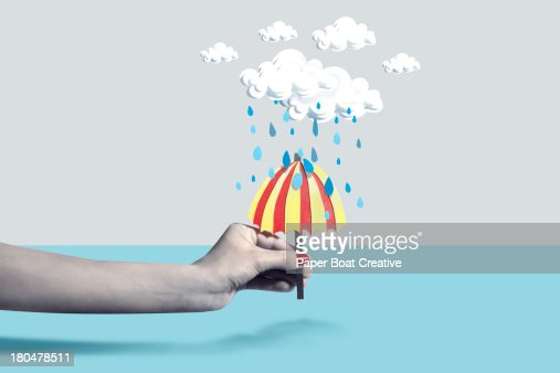 Hand holding paper craft umbrella under rain cloud