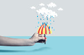 Hand holding paper craft umbrella under rain cloud