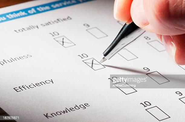 Mão segurando a caneta completar a satisfação do Cliente