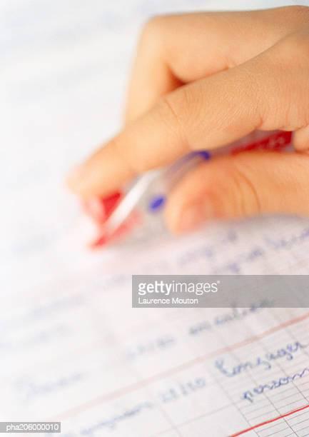 Hand holding pen over school book.