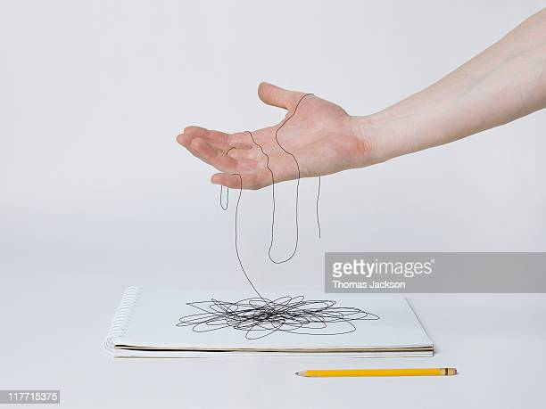 Hand holding pencil lines that turn into thread