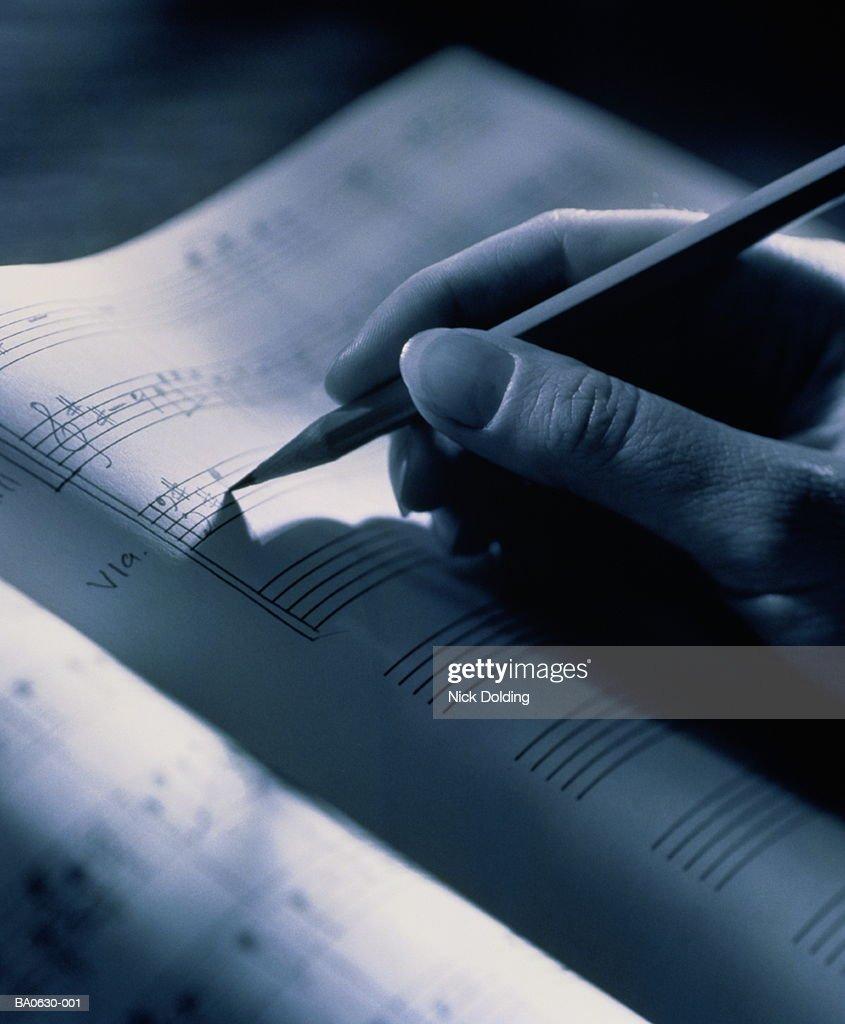 Hand holding pencil, transcribing musical score, close-up, B&W