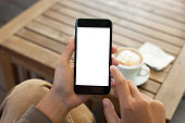 close-up hand holding phone mobile blank screen and finger touching in coffee shop