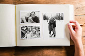 Hand of unrecognizable person holding a photo album looking at various black and white pictures of senior couple. Studio shot on wooden background.