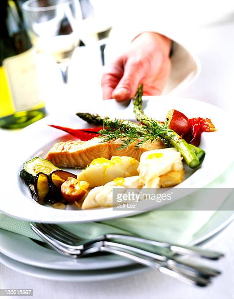 Hand holding plate of seafood & grilled vegetables