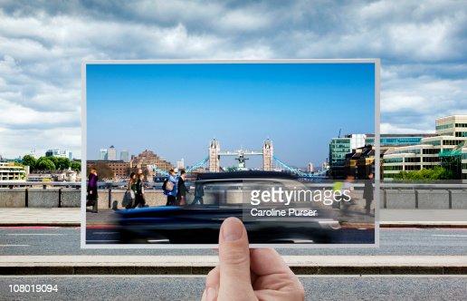 Hand holding postcard of Tower Bridge, London