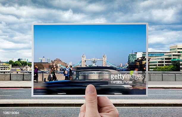 Hand holding postcard of Tower Bridge, London