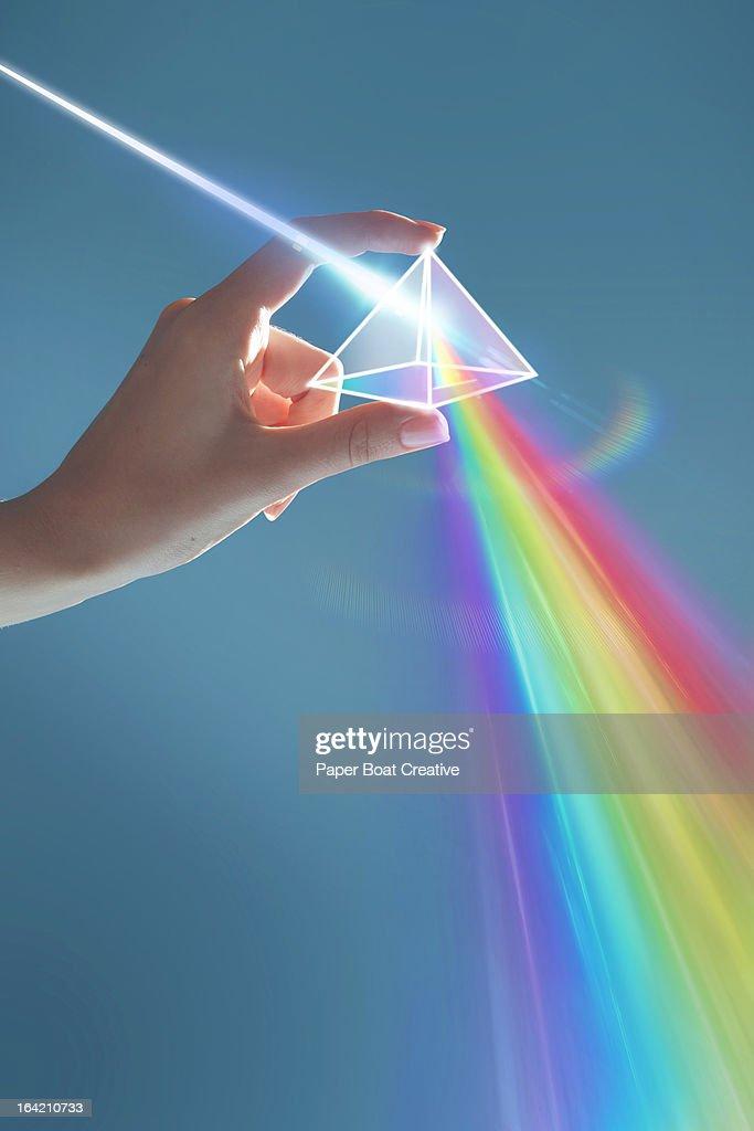 Hand holding rainbow light prism in studio