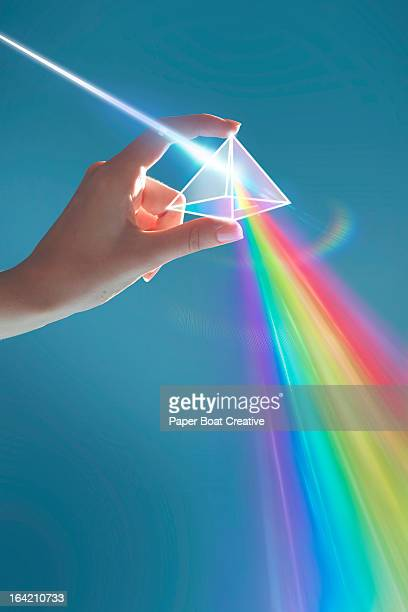 Hand holding rainbow light prism in studio